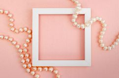 White square frame with pearl beads on a pink pearl design board. Background, paper texture pink color stock photo
