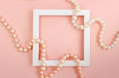 White square frame with pearl beads on a pink pearl design board. Background, paper texture pink color royalty free stock image