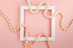 White square frame with pearl beads on a pink pearl design board. Background, paper texture pink color stock photos