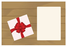White Square Gift Box with Red   Bow on Wooden Plank Background with White sheet of paper. Royalty Free Stock Photos