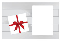 White Square Gift Box with Red   Bow on Wooden Plank Background with White sheet of paper. Stock Image