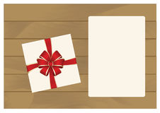 White Square Gift Box with Red   Bow on Wooden Plank Background with White sheet of paper. Royalty Free Stock Images