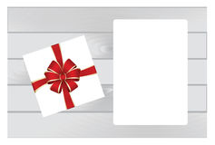 White Square Gift Box with Red   Bow on Wooden Plank Background with White sheet of paper. Royalty Free Stock Photography