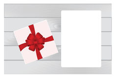 White Square Gift Box with Red   Bow on Wooden Plank Background with White sheet of paper. Stock Images