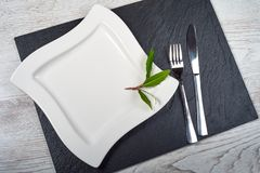White square plate on black slate plate.  Royalty Free Stock Images