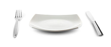 White square plate and cutlery with clipping path. White square plate, knife and fork cutlery isolated with clipping paths included Royalty Free Stock Image