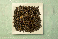 White square plate with a heap of coffee beans Stock Images