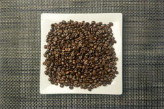 White square plate with a heap of coffee beans Stock Photo