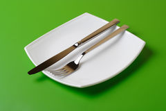 White square plate, knife, and fork Royalty Free Stock Image