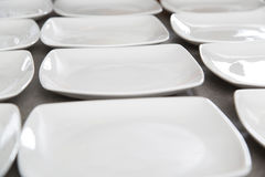 White square plates. Arranged on a table Stock Image