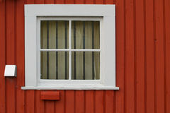 White square window set in a red wooden wall. Small, square white window set into a red wooden siding wall.  The window is barred with curtains drawn Stock Photo