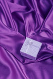 White squared gift box on purple satin fabric folds Stock Images