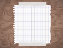 White squared ripped notebook paper sheet, on brown wooden wall, desk Stock Photos