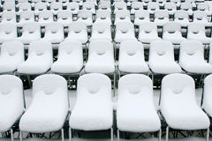White stadium chairs covered in snow Stock Photo