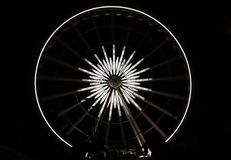 White star ferris wheel brightly lit at amusement park at night,. Dark background Stock Photos