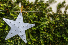 White star hanging on a rope, with a green background Royalty Free Stock Image