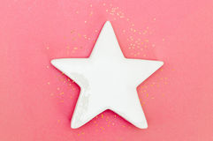 White star on pink background. White ceramic star on pink background, with golden star-shaped glitter. Space for text Royalty Free Stock Photos