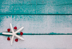 White starfish and red hearts on sandy teal blue sign Royalty Free Stock Photography