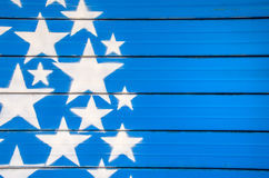 White stars on blue background painted on a closed shutter Royalty Free Stock Image