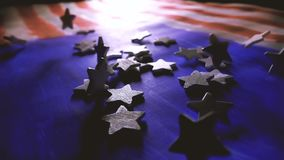 White stars falling on painted American flag, the symbol of the United States of America. Super slow motion shot stock footage