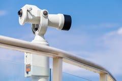 White stationary paid telescope on sea coast Stock Photo