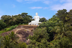 White statue of seated Buddha (Siddharta Gautama). With a raised right hand in a gesture of vitarka on the hill on Mihintale Royalty Free Stock Image