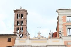 Statues and cross. White statues of saints and metal cross on top of building with high tower behind in Rome, Italy Stock Photo