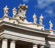 White statues on top of Vatican building, blue sky. Big white statues placed on the top of a Vatican building, with almost clear sky on the background Stock Image