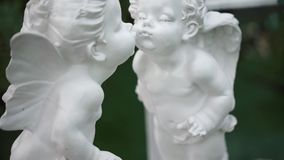 White statues of two kissing angels. The camera moves from the bottom up. The Big Day stock footage