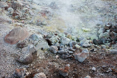 White steam raising over colored sulfur rocks, Iceland Stock Images