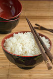 White steamed rice in a bowl with chopsticks Royalty Free Stock Photos