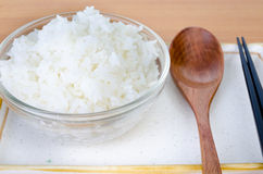White steamed rice in bowl with chopsticks and wood spoon . Stock Photo