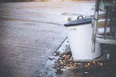 A white steel garbage bin with black covering outside house. By the street Royalty Free Stock Image