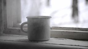 The white steel mug with boiling water near the window stock video footage