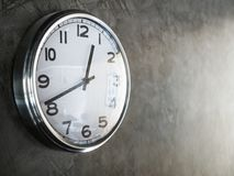 White steel round clock on grey concrete wall. White steel round shape clock on grey concrete wall with copy space royalty free stock photography