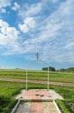 White steel semi-circular arch with an orthodox cross on it on the background of the rural landscape under a blue sky with clouds Stock Photography