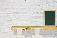 Steel Stools with Wooden Shelf and Blank Black Chalkboard on White Brick Wall Background. White Steel Stools with Wooden Shelf and Blank Black Chalkboard on stock images