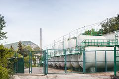 White steel tanks behind green fence Stock Image