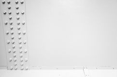 White steel wall with bolts in a row, metal parts Royalty Free Stock Photography