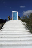 White steps to a blue door on santorini island Stock Image