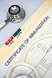 White stethoscope on a medical chart. With a certificate of immunization stock photography