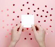 White sticker in female hands on pink background with hearts. stock images