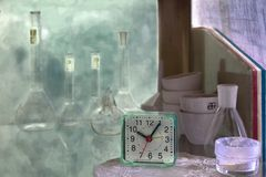 White still life with a clock. Production still life in white with a chemical theme. Old alarm clock. Flasks royalty free stock photography