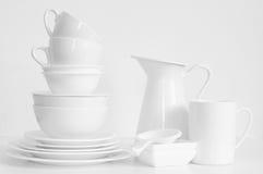 White still life. Minimalistic still life: set of simple elegant white tableware on white background. Soft light, high key royalty free stock image