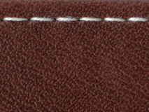 White stitch. Straight white stitch over the leather material surface royalty free stock image