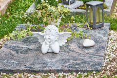 Angel on a marble plate. White stone angel on a marble plate with a heart and a grave lantern in memorial Royalty Free Stock Photo