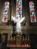 A white stone angel and story-telling glass behind inside the Sacré-Cœur, Paris royalty free stock photos
