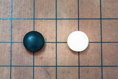 White stone approach to black stone on go game board. Top view closeup white stone approach to black stone on go game board, traditional chinese strategy board Royalty Free Stock Photo