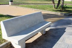 White stone bench and green space stock images