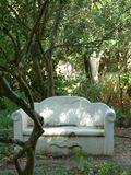 A white stone bench in the woods stock images